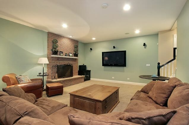 basement with a fireplace, tv on wall, sectional and coffee table