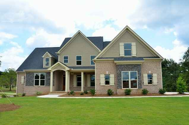 front of large house with 12 windows, 3 pillars and some brick siding