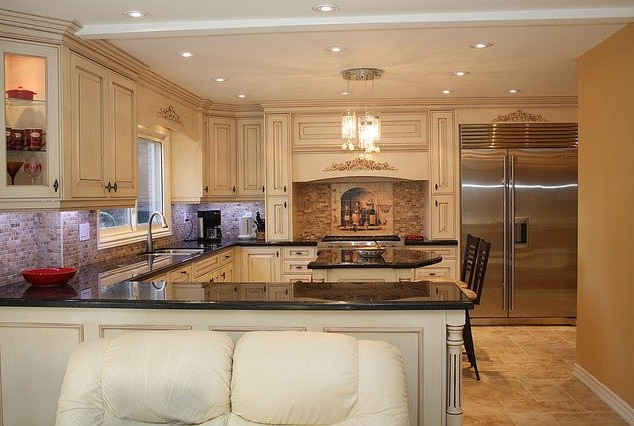 kitchen with black granite tops, an island, custom cabinets stainless fridge